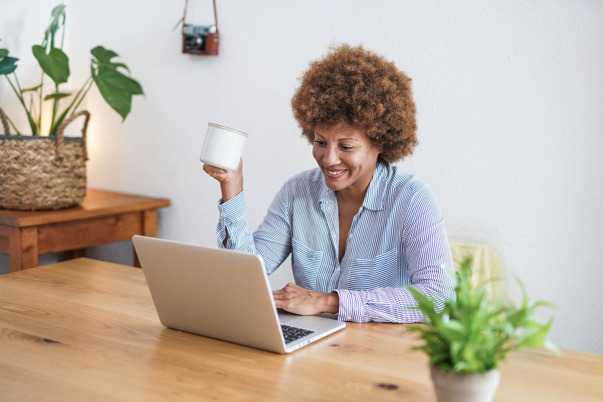 Mature african woman working from home with computer laptop