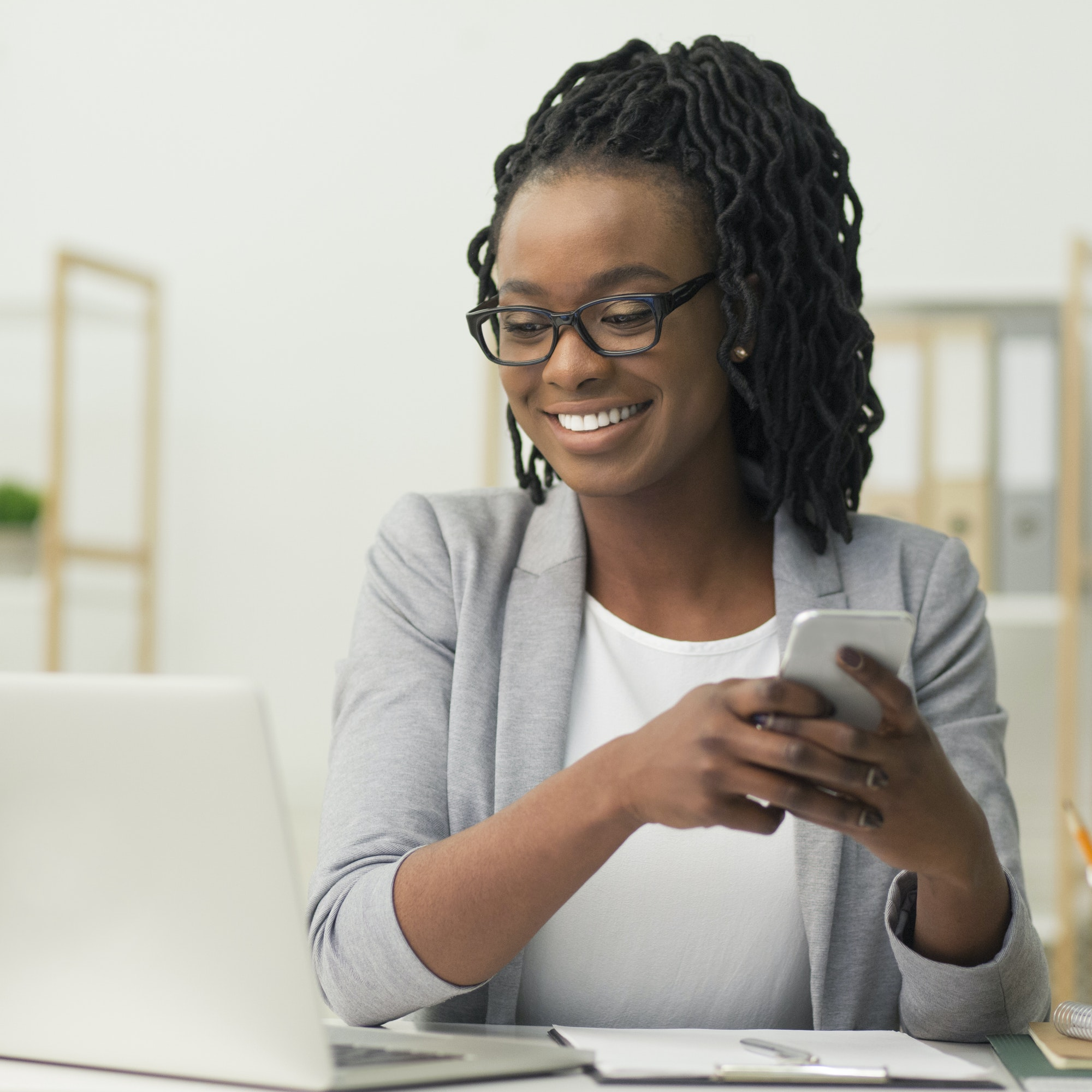 Afro Businesswoman Texting Via Smartphone Sitting In Modern Office