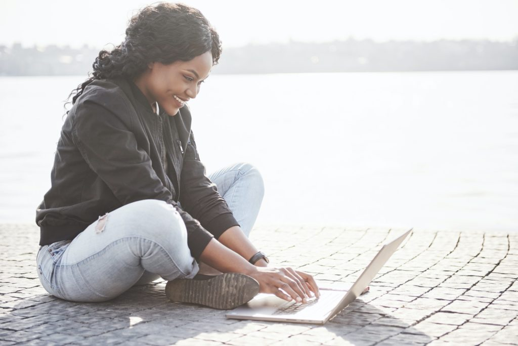 Young woman on the street working on laptop